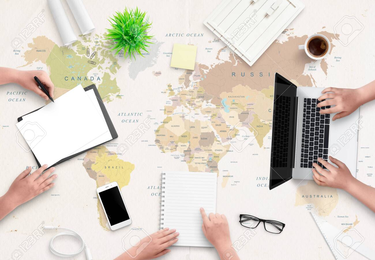 Two people working at a desk with a laptop and notepad on top of a world map